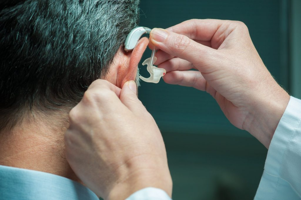 ent doctor putting on hearing aid for patient